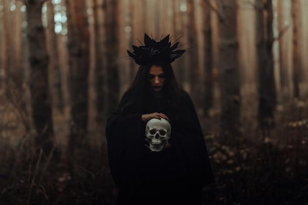 숲에서 검은 의상 마녀 소녀의 어두운 초상화