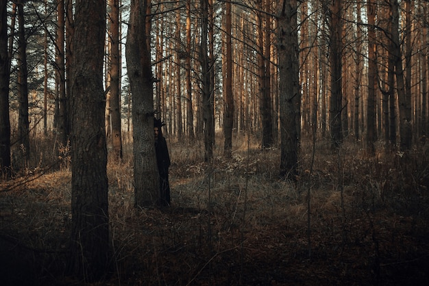 Dark portrait of a terrible witch in a black suit in the forest by a tree