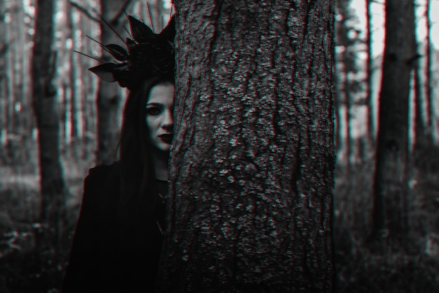 Dark portrait of a witch girl in a black costume in the woods. black and white with 3d glitch virtual reality effect