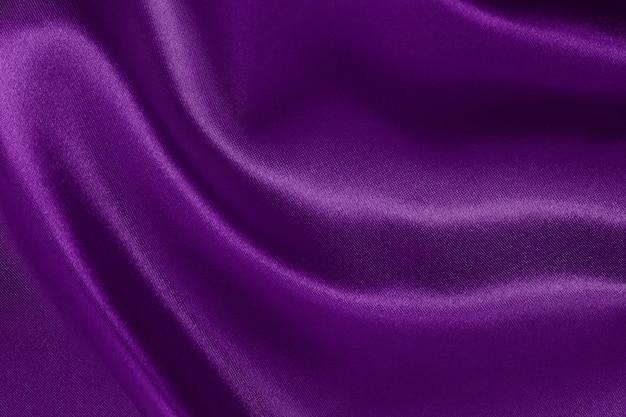 濃い紫色の生地のテクスチャ背景、シルクやリネンのしわくちゃのパターン。