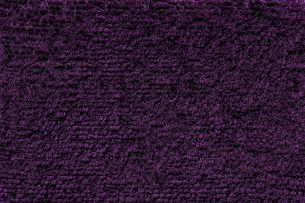 Dark purple fluffy background of soft, fleecy cloth. texture of textile closeup