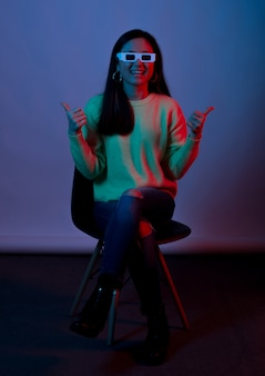 Dark purple photo of a young woman wearing 3d glasses for cinema