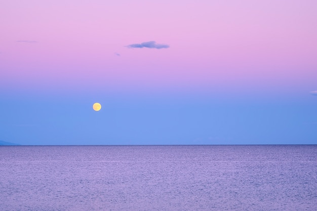 Dark purple sky with yellow moon over sea after sunset in greece