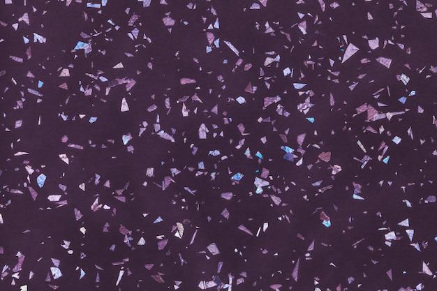 小さなホイルスパンコール、クローズアップから濃い紫色の輝く背景。小さなパン粉のパターンと紫のテクスチャ背景。