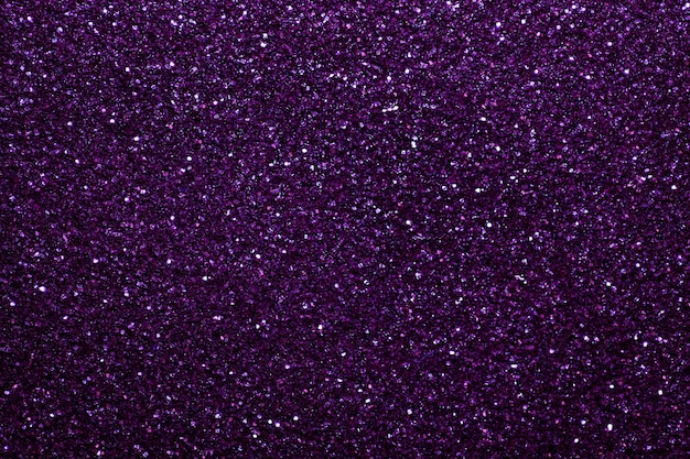 Dark purple sparkling background from small sequins, closeup