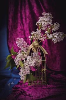라일락 꽃과 금 새장에 가지와 어두운 보라색 벨벳 커튼 빈티지 배경