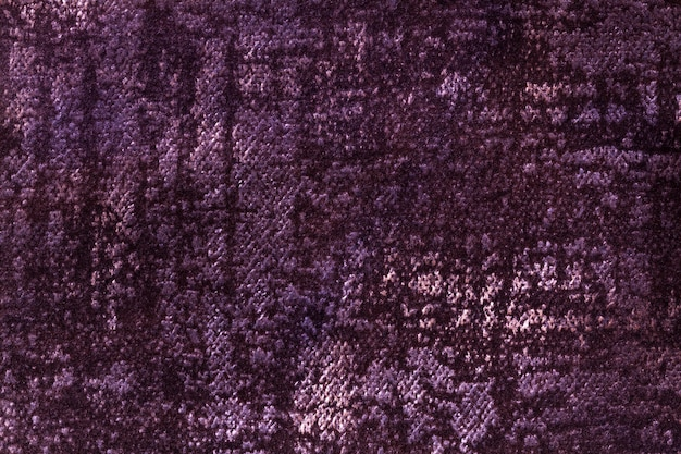Dark purple and violet fluffy background of soft, fleecy fabric. texture of wine textile backdrop with shiny pattern, closeup.