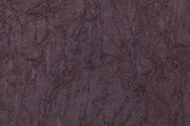 Dark purple wavy background from a textile material. fabric with natural texture closeup.