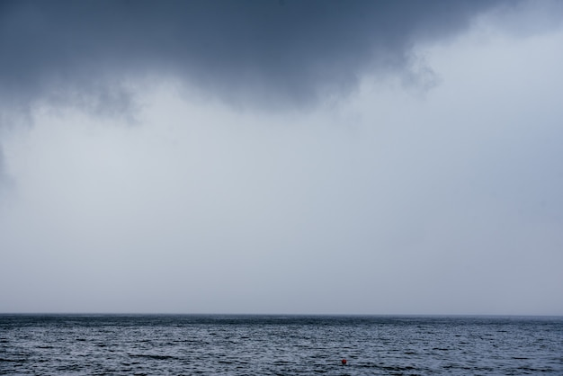 Dark rainy clouds over the sea surface landscape