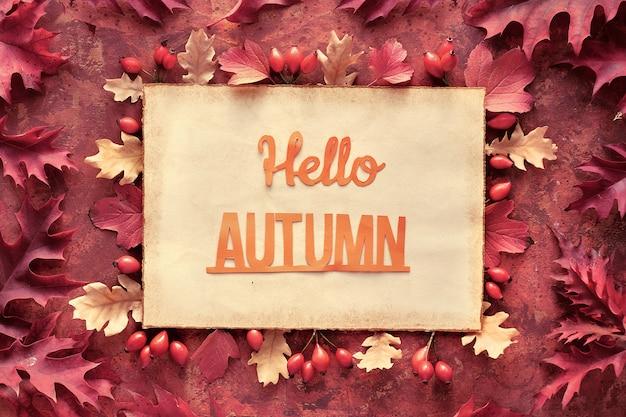 オークの紅葉の飾り枠が入ったダークレッドとブラウンの秋フレーム。手作りの羊皮紙にテキストこんにちは秋をカット
