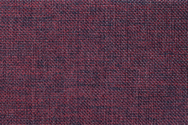 Dark red background of dense woven bagging fabric, closeup.