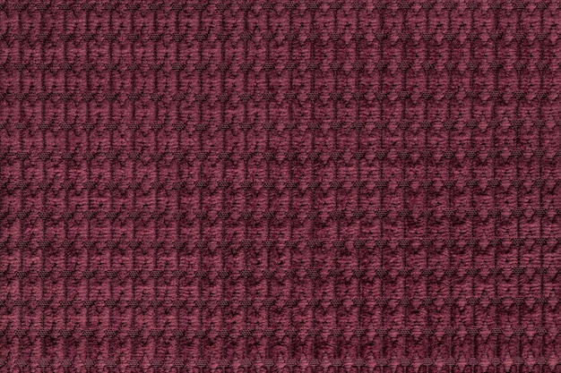 Dark red background from soft fleecy fabric close up. texture of textiles macro