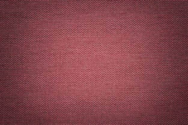 Dark red background from a textile material. fabric with natural texture.
