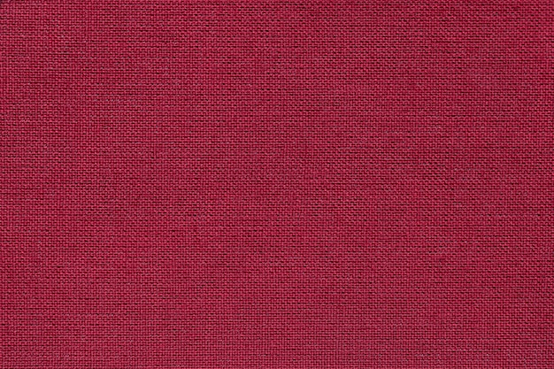 Dark red background from a textile material with wicker pattern, closeup.