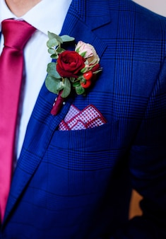 Dark red boutonniere pinned to groom's blue jacket