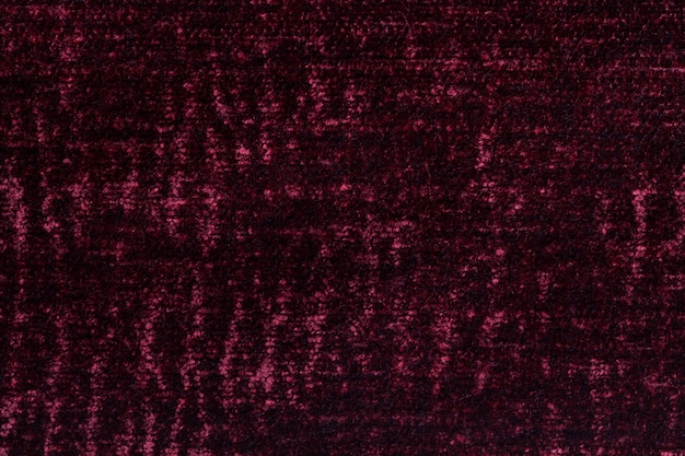 Dark red fluffy background of soft, fleecy cloth, texture of textile closeup