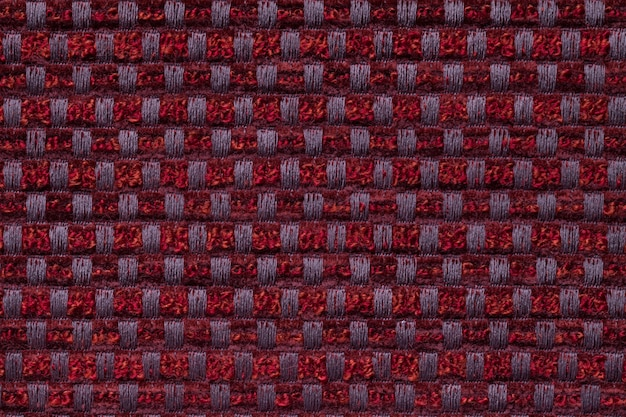 Dark red from checkered pattern textile, closeup. structure of the wicker fabric macro.