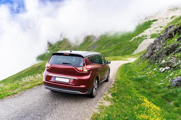 비오는 날씨에 프랑스 산 높은 구불구불한 도로에 짙은 빨간색 해치백 가족용 자동차. 알프스 가족 여행. 구름이 자동차를 둘러싸고 있습니다.