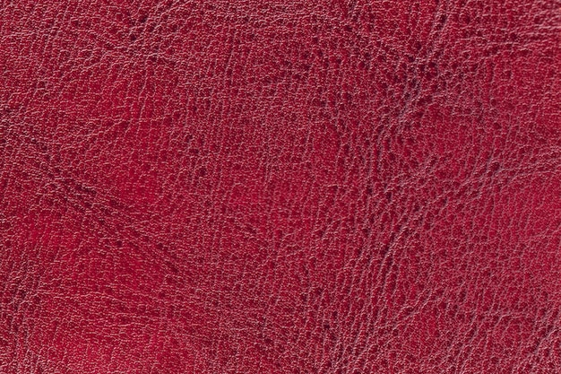Dark red leather texture background, closeup. ruby cracked backdrop from wrinkle skin