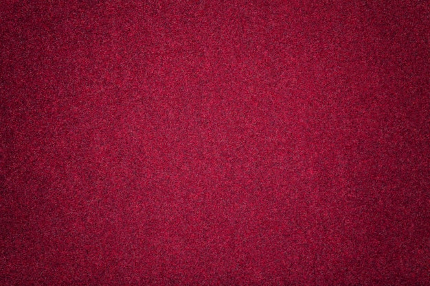 Dark red matt suede fabric closeup. velvet texture of felt.