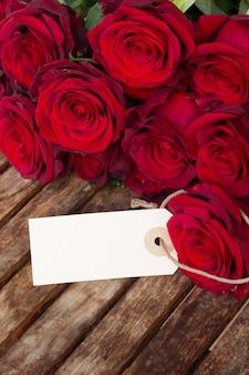 濃い赤のバラと木製のテーブルのタグ