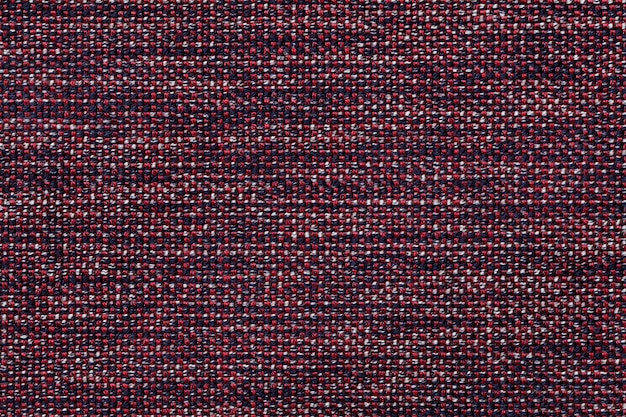 Dark red textile background with checkered design, closeup. structure of the fabric macro.