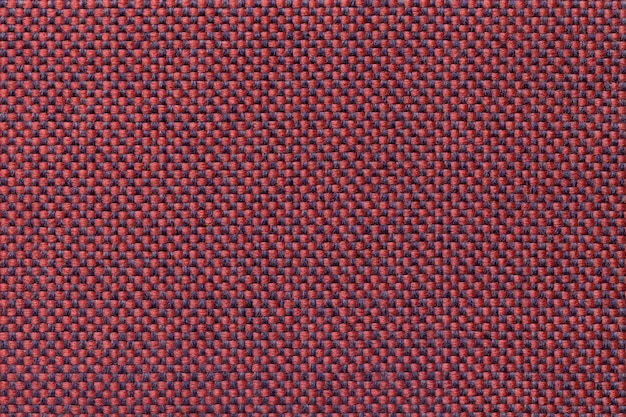 Dark red textile background with checkered pattern, closeup. structure of the fabric macro.