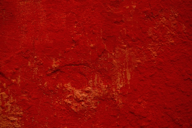 Dark red  texture of a painted wall with rough surface and stains in a full frame view.