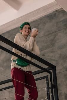 ダークレッドのパンツ。お茶を飲む深紅のズボンを着た緑髪のスタイリッシュな若い女性
