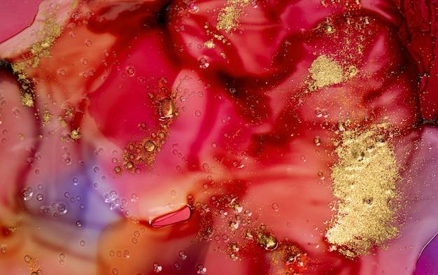 거품과 금 입자가 있는 투명한 액체 아래 진한 빨간색 수채화 잉크 얼룩.