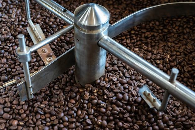 Dark roast coffee beans mixing roasted coffee , coffee roasting machine background texture