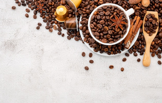 Dark roasted coffee beans and capsules with scoops setup on white concrete