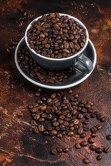 블랙 컵에 어두운 볶은 커피 콩. 평면도.