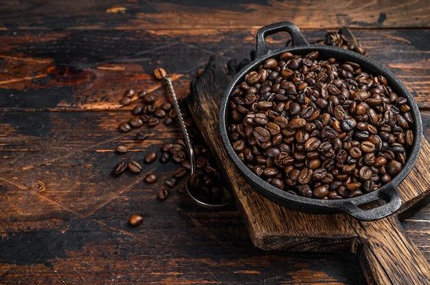 나무 테이블에 냄비에 어두운 볶은 커피 콩. 평면도.