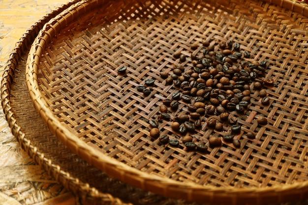 Темные обжаренные кофейные зерна в плетеной корзине перед просеиванием для приготовления домашнего кофе