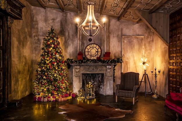 クリスマスインテリアの暗い部屋、点滅する花輪で飾られたクリスマスツリー。人工暖炉で装飾を暗くする