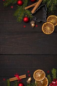 Dark rustic wooden background with christmas decoration, fir frame.