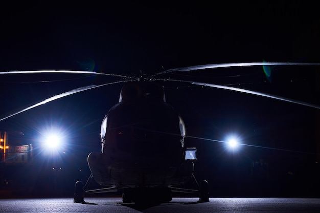 Dark silhouette of big military helicopter, highlighted with two white lights.