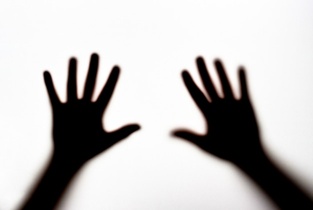 Dark silhouette of female hands on white background, concept of fear