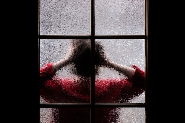 Dark silhouette of girl in red behind glass.