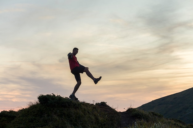 Dark silhouette of a hiker balancing on a summit stone in evening mountains.