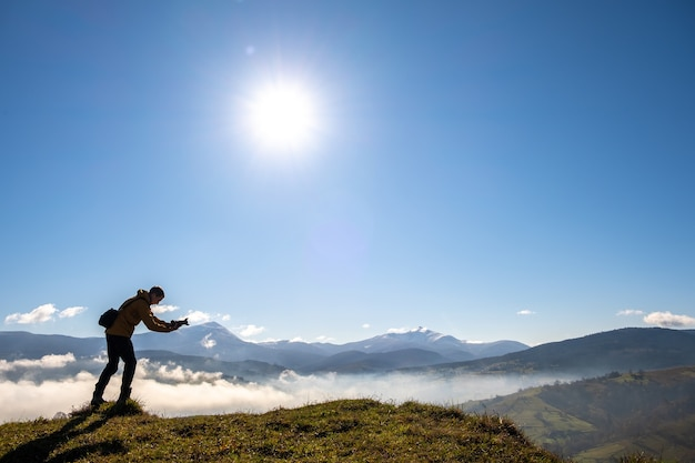 Dark silhouette of a hiker photographer taking picture of morning landscape in autumn mountains.