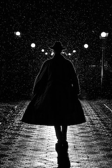 Dark silhouette of a man in a coat and hat in the rain on a night street in the city in the style of noir