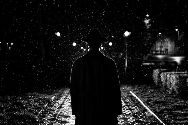 Dark silhouette of a man in a hat in the rain on a night street in a city in the style of noir