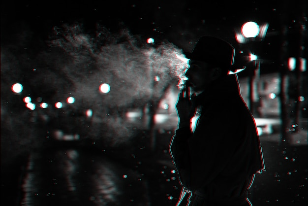 Dark silhouette of a man in a hat smoking a cigarette in the rain on a night street. black and white with 3d glitch virtual reality effect