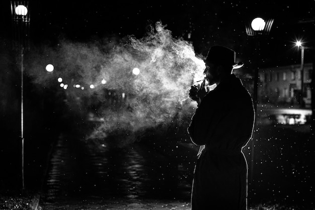 Dark silhouette of a man in a hat smoking a cigarette in the rain on a night street in the style of noir Premium Photo