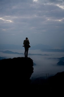 Dark silhouette of man photographer on the cliff and beauty mist at morning.