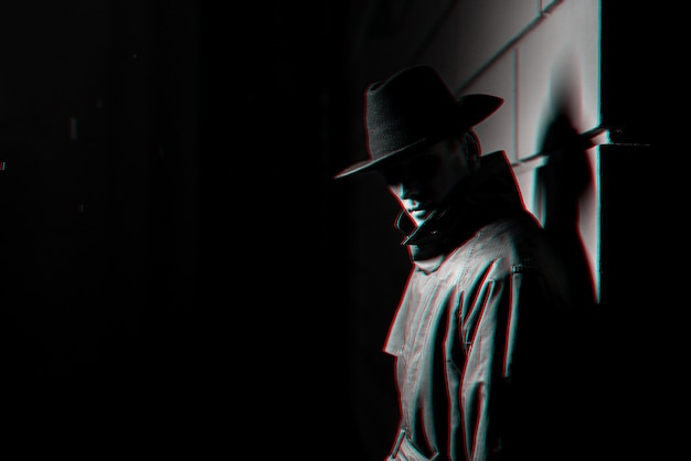 Dark silhouette of a man in a raincoat with a hat at night. black and white with 3d glitch virtual reality effect