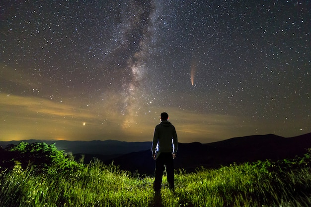 Dark silhouette of a man standing in mountains at night enjoying milky way and neowise comet with light tail in dark sky view.