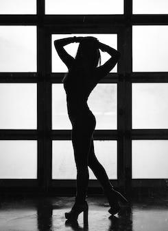 小さな窓の背景に立っている女の子の暗いシルエット